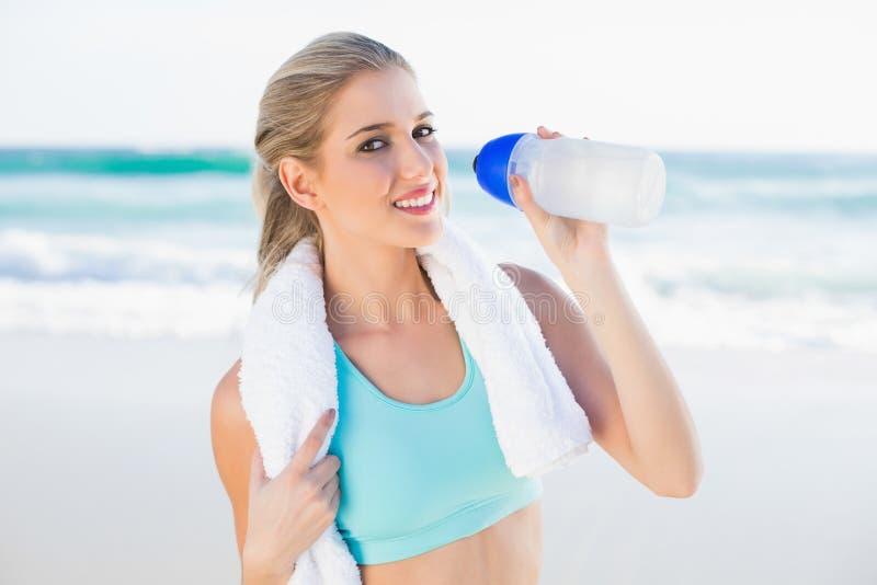 Bionda adatta sorridente in acqua potabile degli abiti sportivi immagine stock libera da diritti