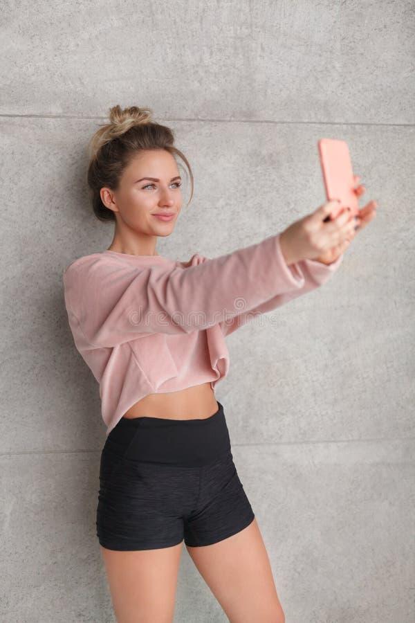 Bionda allegra esile che prende selfie fotografia stock