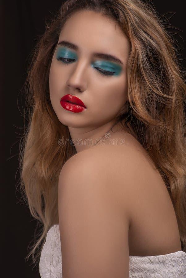 Bionda attraente con trucco alla moda luminoso Occhi affumicati colorati con effetto bagnato della palpebra Ritratto di modo sul  fotografia stock