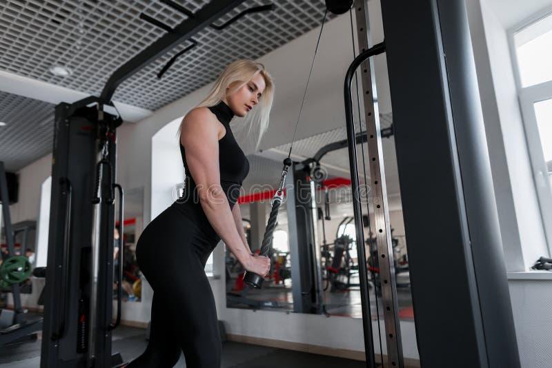 Bionda attraente della giovane donna in abiti sportivi che fanno gli esercizi di forza per le mani per mezzo del simulatore moder fotografia stock libera da diritti