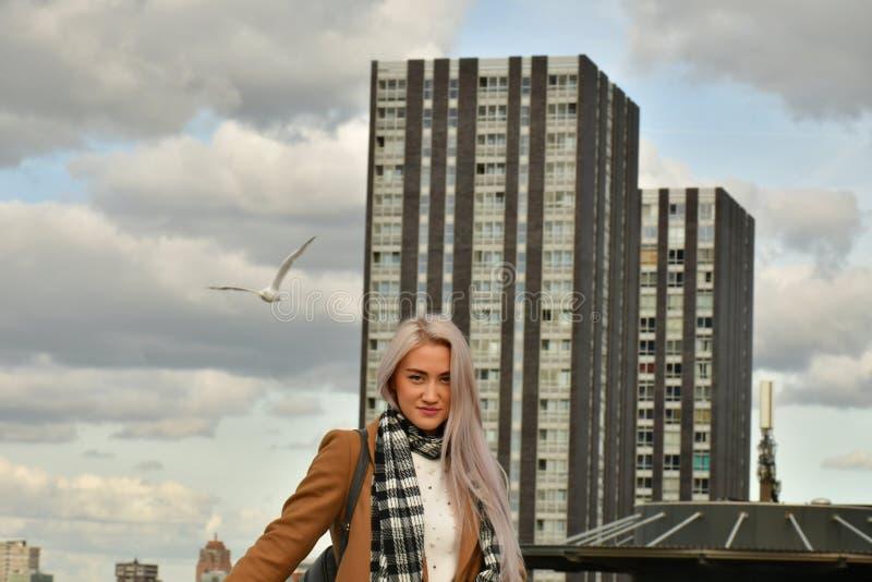 Bionda in cappotto sul tetto del grattacielo fotografia stock