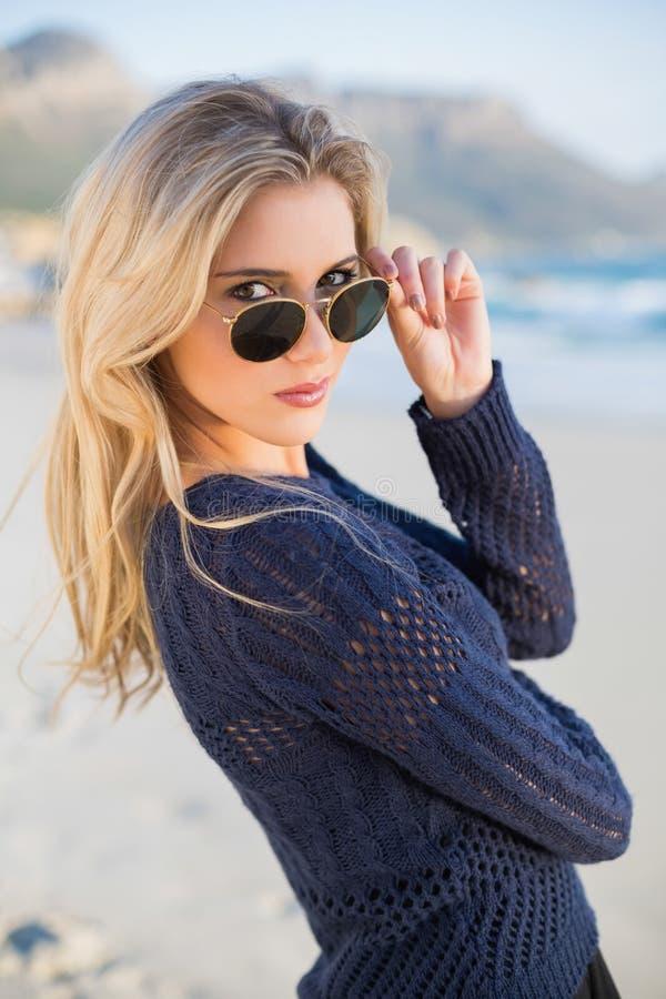 Bionda casuale attraente che esamina i suoi occhiali da sole immagine stock libera da diritti