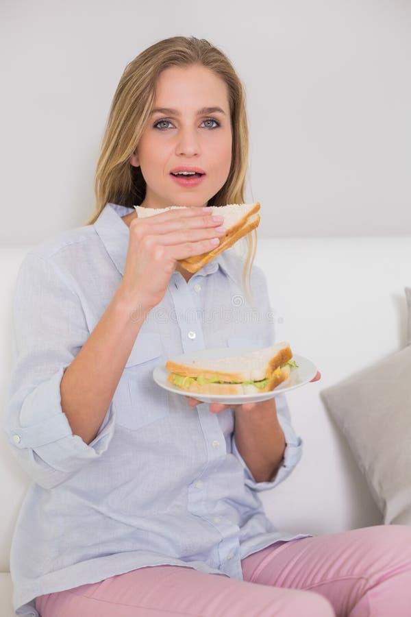 Bionda casuale contenta che si siede sul panino della tenuta dello strato fotografia stock libera da diritti
