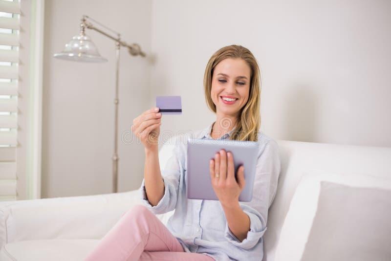 Bionda casuale sorridente che per mezzo della compressa per l'acquisto online fotografia stock libera da diritti