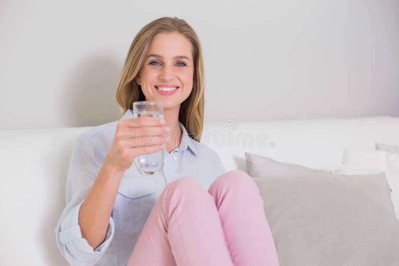 Bionda casuale sorridente che si siede sullo strato che tiene bicchiere d'acqua fotografia stock libera da diritti