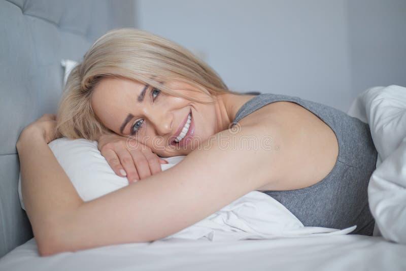 Bionda casuale sorridente che si trova nel suo letto in camera da letto luminosa fotografie stock libere da diritti