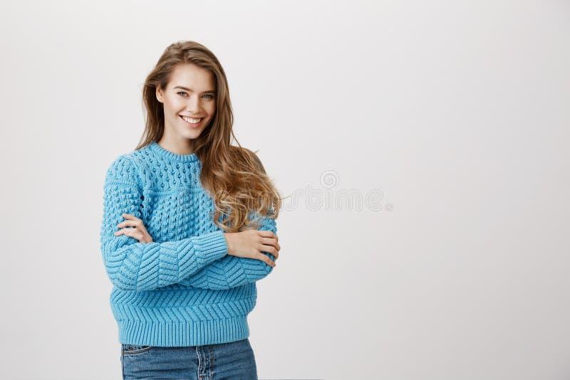 Bionda caucasica sicura e riuscita che sta con le mani attraversate ed il sorriso positivo, danti un'occhiata alla macchina fotog fotografie stock libere da diritti