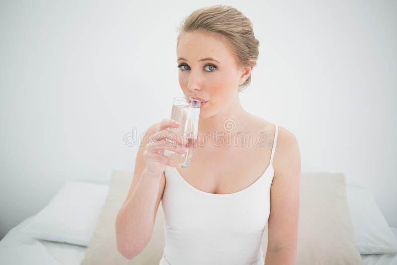 Bionda contenta naturale che beve un bicchiere d'acqua immagine stock