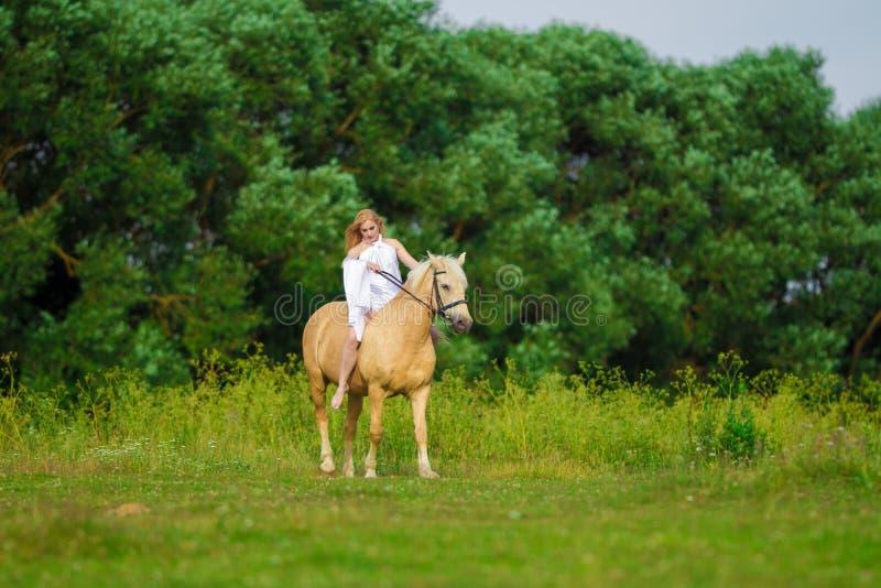 Bionda della donna dell'utente con capelli lunghi in un vestito bianco con un treno che posa su un cavallo di palamino immagine stock