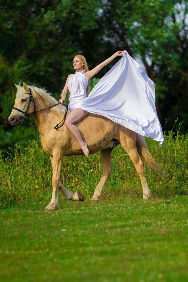 Bionda della donna dell'utente con capelli lunghi in un vestito bianco con un treno che posa su un cavallo di palamino fotografia stock