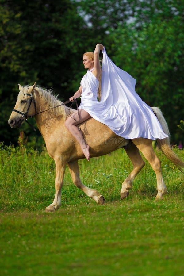 Bionda della donna dell'utente con capelli lunghi in un vestito bianco con un treno che posa su un cavallo di palamino immagini stock