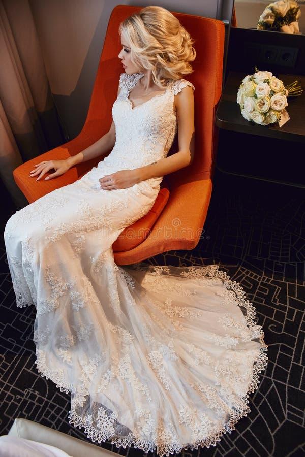 Bionda della sposa in vestito da sposa bianco che si siede in una sedia in una camera di albergo Donna che riposa prima della cer fotografia stock libera da diritti