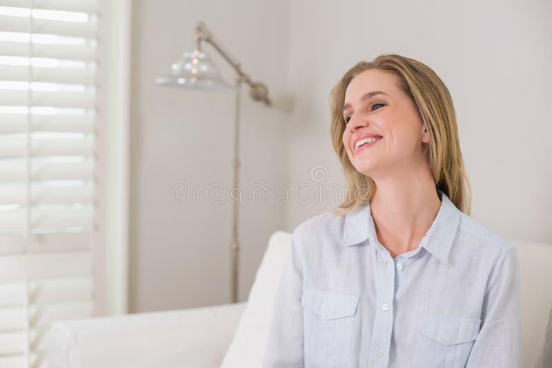 Bionda di risata casuale che si siede sul distogliere lo sguardo dello strato fotografie stock