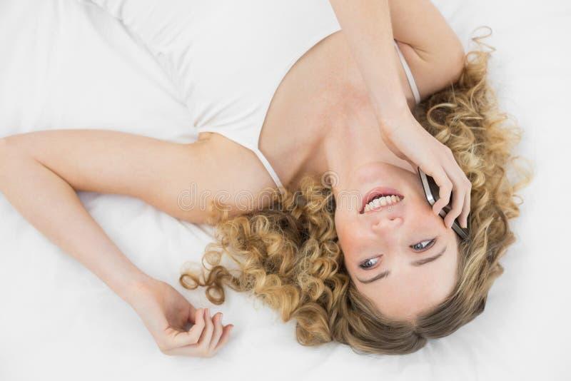 Bionda di risata graziosa che si trova sul letto che telefona con il telefono cellulare fotografia stock