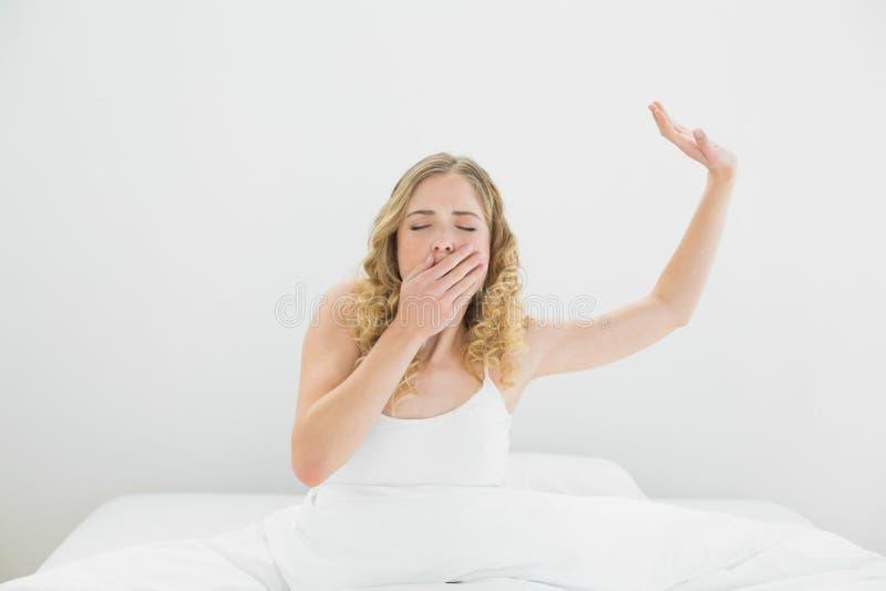 Bionda di sbadiglio graziosa che si siede a letto coprendo la sua bocca fotografia stock