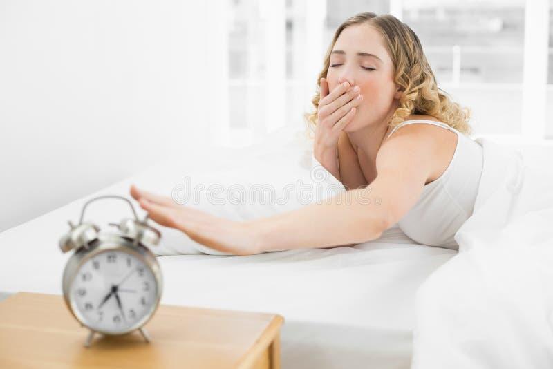Bionda di sbadiglio graziosa che si trova a letto raggiungendo per la sveglia immagini stock libere da diritti