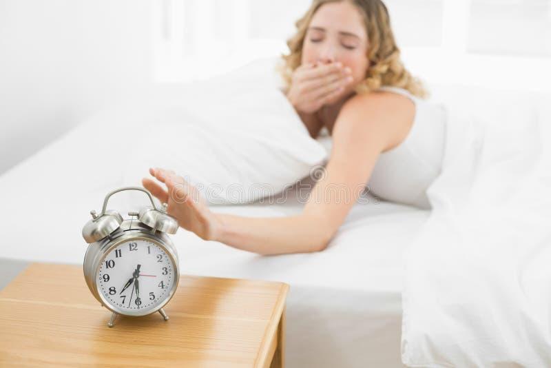 Bionda di sbadiglio graziosa che si trova a letto spegnebbi sveglia fotografia stock libera da diritti