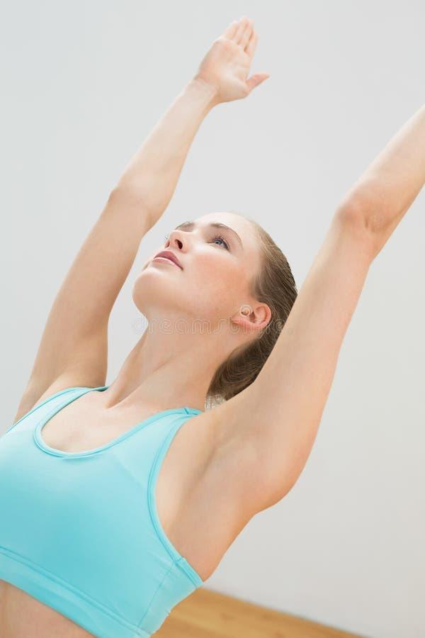 Bionda esile Unsmiling che sta nella posa di yoga immagine stock libera da diritti