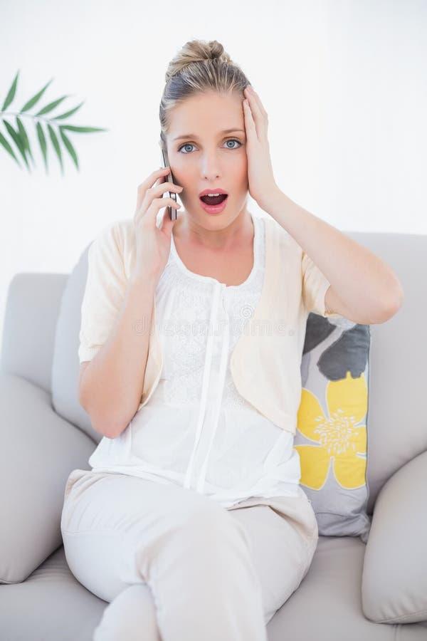 Bionda fresca colpita in vestiti bianchi sul telefono immagini stock libere da diritti