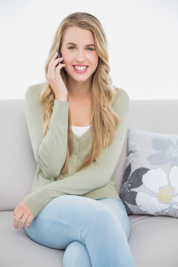 Bionda graziosa felice sul telefono che si siede sul sofà accogliente fotografia stock libera da diritti