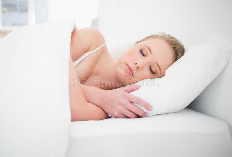 Bionda graziosa naturale che dorme a letto fotografia stock