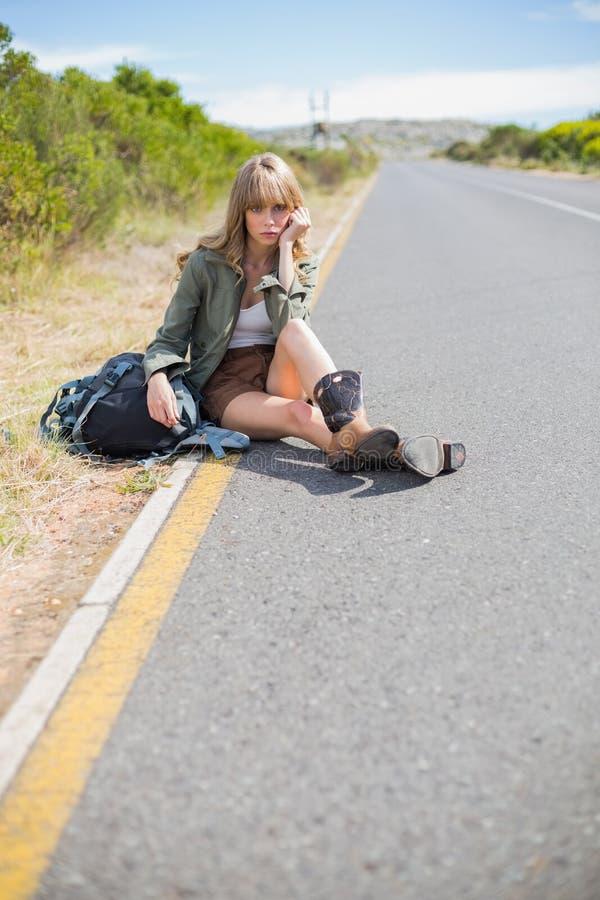 Bionda graziosa stanca che si siede sul bordo della strada immagini stock
