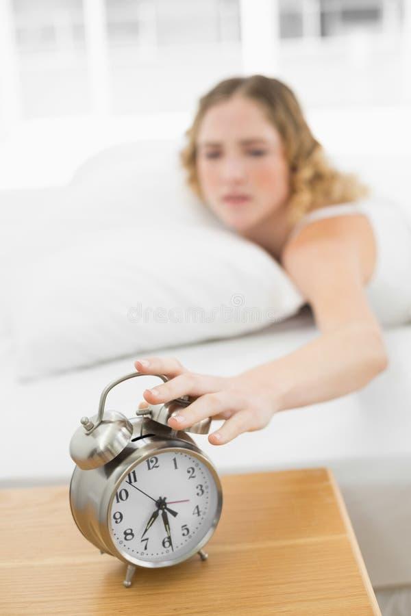 Bionda infastidita graziosa che si trova a letto spegnebbi sveglia immagine stock