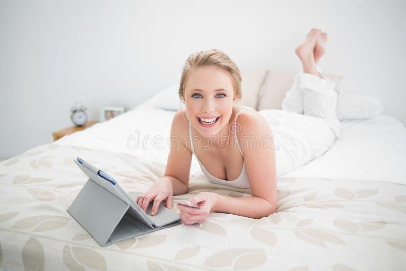 Bionda naturale sorridente che si trova sul letto e sul per mezzo della compressa immagine stock