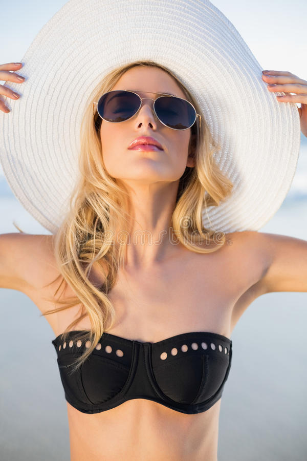 Bionda sensuale pacifica nella posa nera elegante del bikini immagine stock