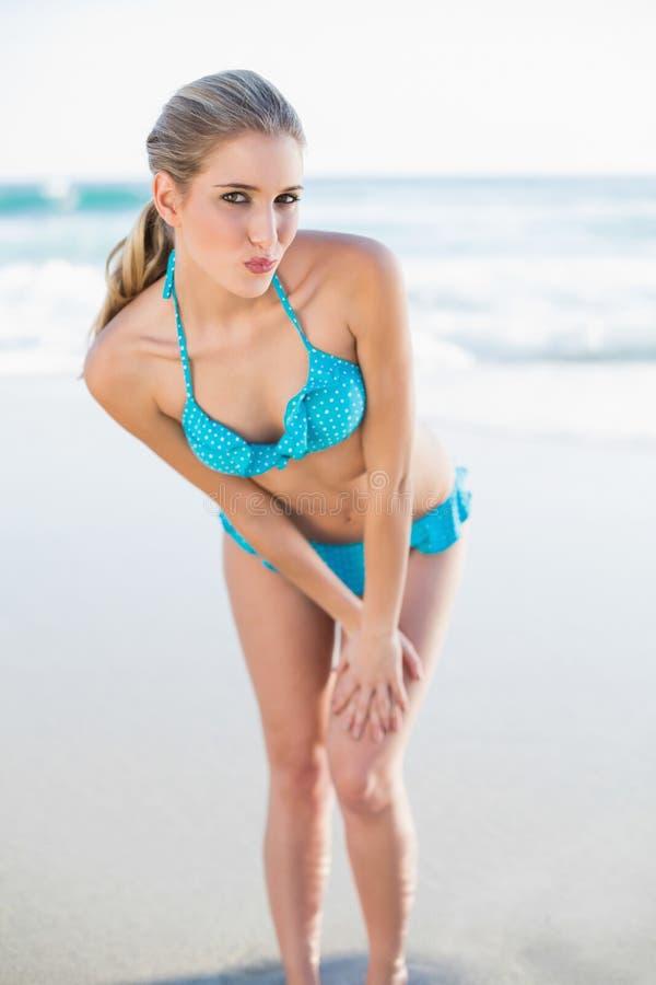 Bionda sexy allegra in bikini che invia un bacio dell'aria alla macchina fotografica immagini stock