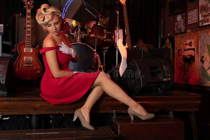 Bionda sexy che si siede su una fase davanti agli strumenti musicali fotografia stock