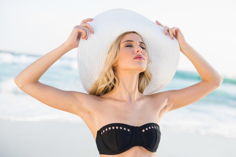 Bionda sexy rilassata nella posa d'uso del cappello di paglia del bikini elegante fotografie stock libere da diritti