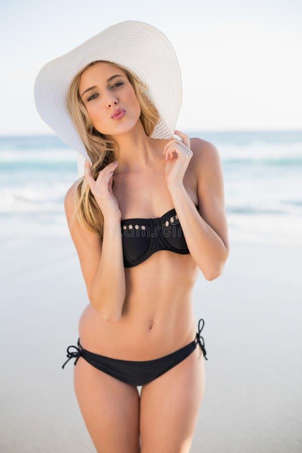 Bionda sexy sorridente nel baciare d'uso del cappello di paglia del bikini elegante fotografie stock