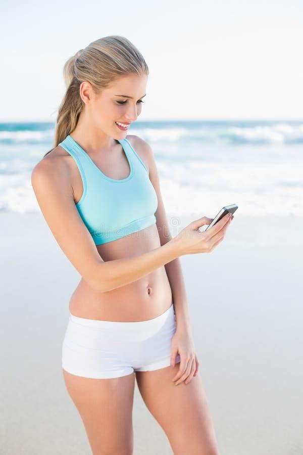 Bionda snella sorridente nel mandare un sms degli abiti sportivi fotografia stock