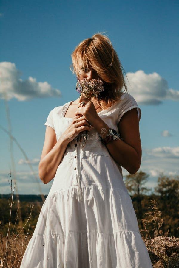Bionda snella in vestito bianco che fiuta i fiori selvaggi fotografie stock libere da diritti