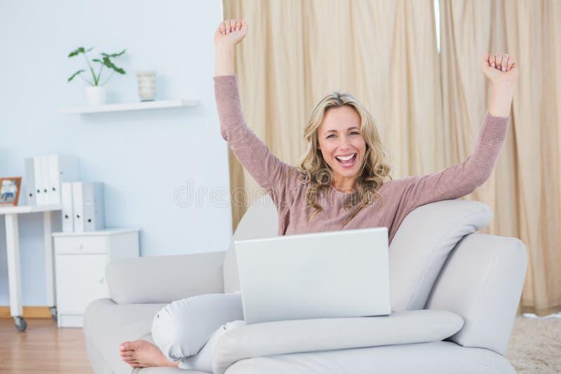 Bionda sorridente che incoraggia e che per mezzo del computer portatile fotografia stock libera da diritti