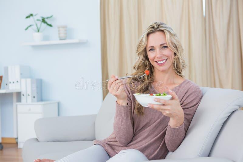 Bionda sorridente che si siede sullo strato che mangia insalata immagini stock