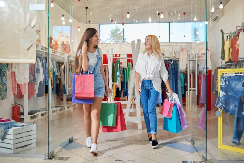 Bionda sorridente e negozio di vestiti uscente castana immagine stock