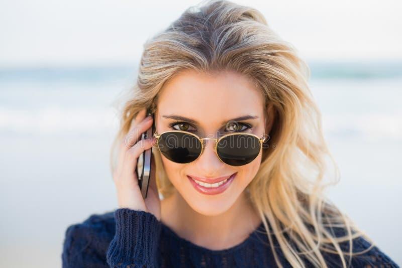 Bionda splendida allegra sul telefono che esamina il suo sunglasse immagine stock