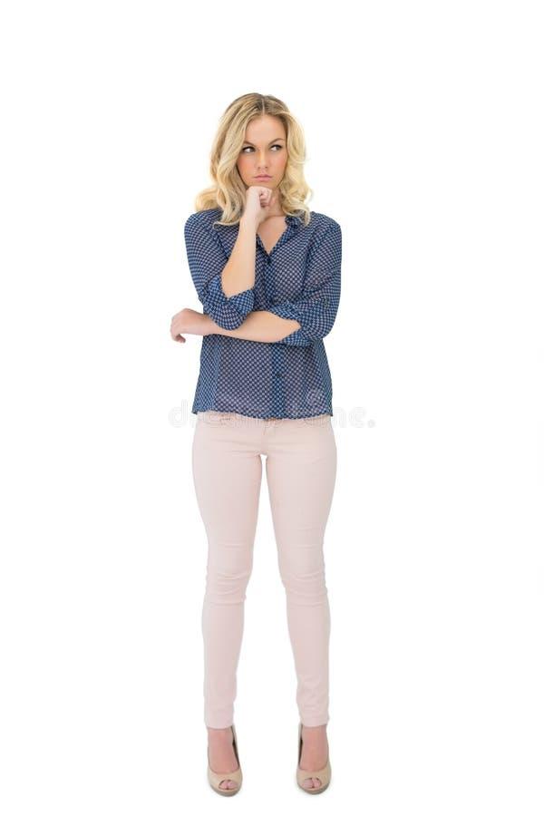 Bionda splendida pensierosa che indossa posa di classe dei vestiti immagine stock libera da diritti