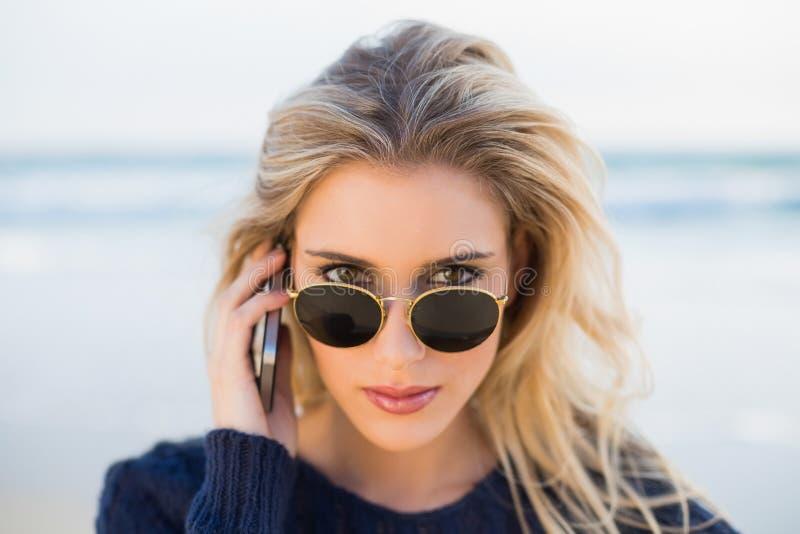 Bionda splendida seria sul telefono che esamina i suoi occhiali da sole immagini stock libere da diritti