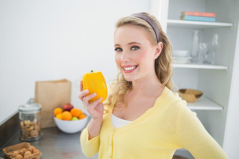 Bionda sveglia allegra che tiene un pepe giallo immagine stock