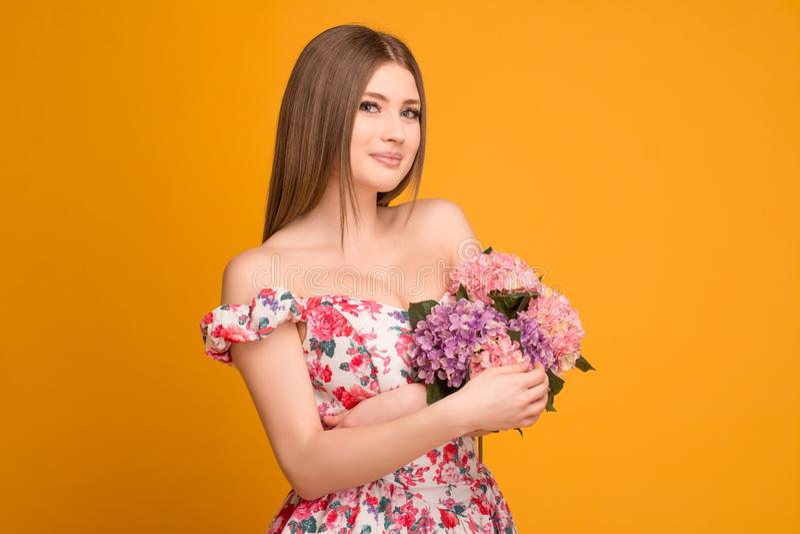 Bionda in un vestito con un mazzo dei fiori fotografia stock libera da diritti