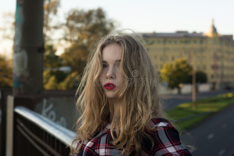 Bionda in una camicia di plaid in tempo ventoso sulle strade ferrate fotografie stock libere da diritti
