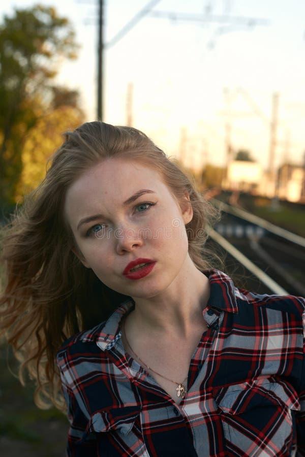 Bionda in una camicia di plaid in tempo ventoso sulle strade ferrate fotografia stock libera da diritti