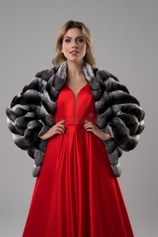 Bionda in vestito rosso ed in colpo potato pelliccia fotografie stock