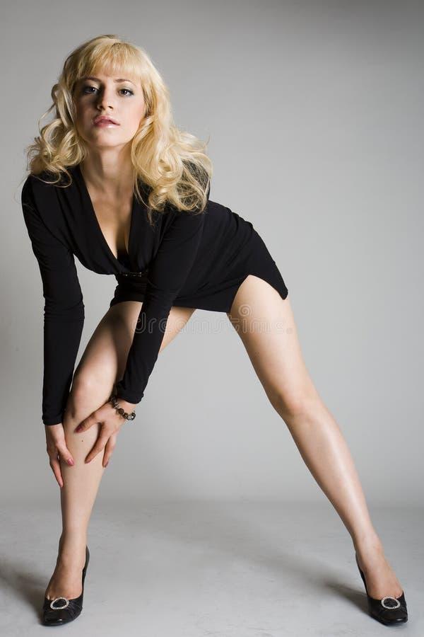 Biondo sexy alla moda in breve vestito nero immagine stock