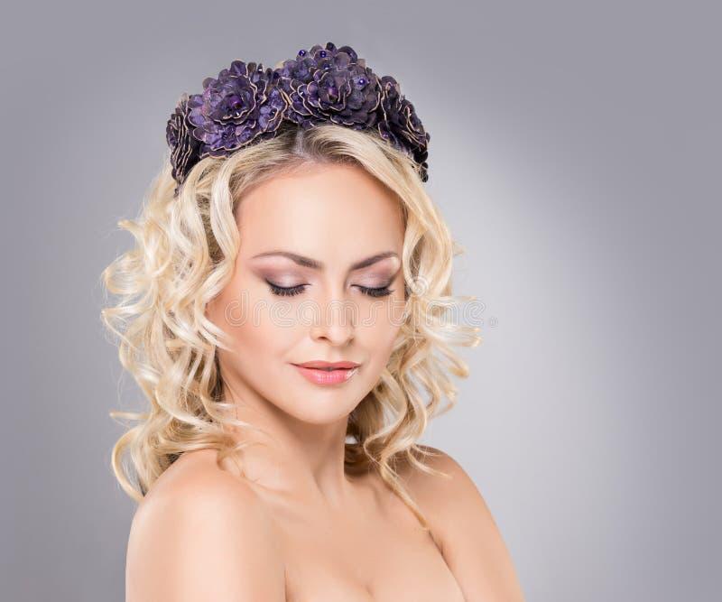 Biondo splendido indossando una corona porpora del fiore fotografia stock