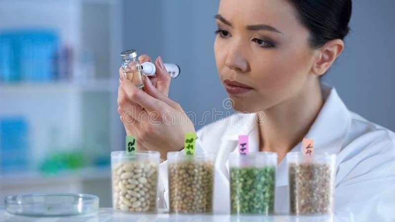 Bioquímico asiático que hace las notas en la ampolla con el líquido químico, pesticidas foto de archivo