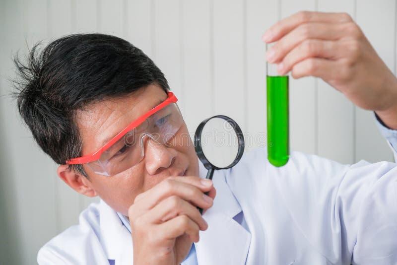 Bioquímico en el trabajo Hombre confiado en la tenencia protectora de las gafas imagenes de archivo